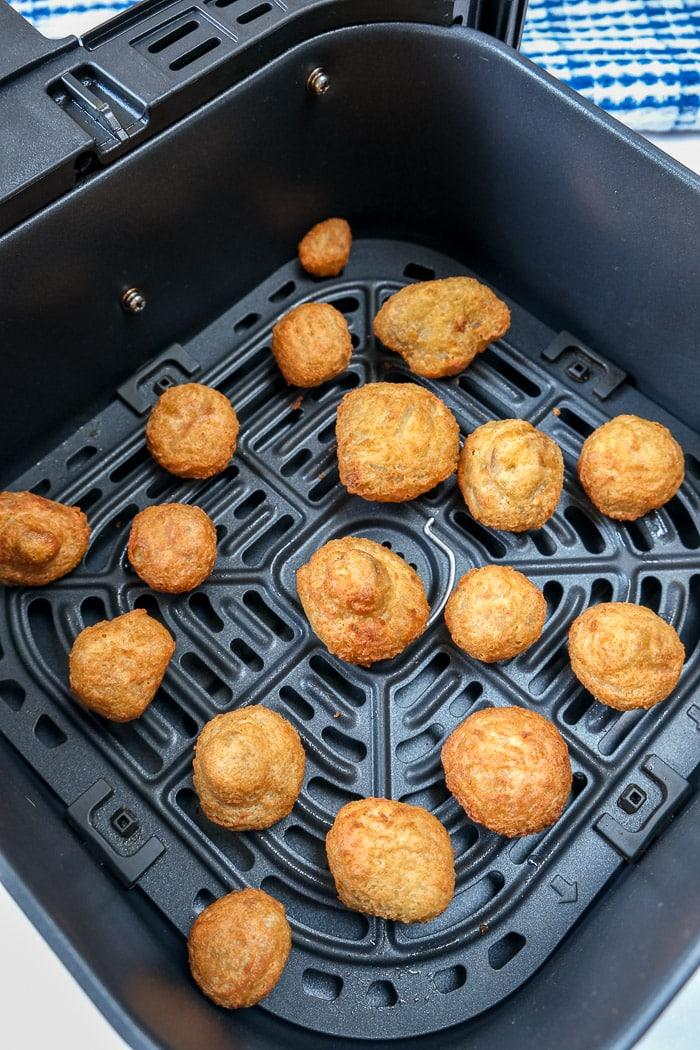 crispy breaded mushrooms in black air fryer tray on counter