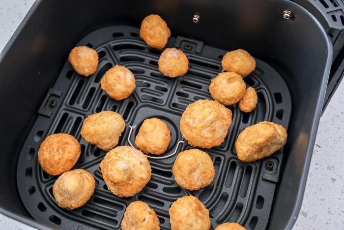 frozen battered mushrooms in black air fryer tray