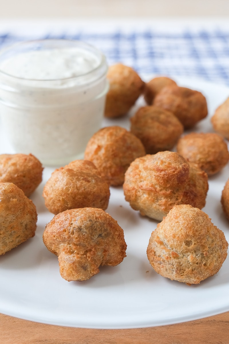 battered mushrooms on white plate with white dipping sauce behind
