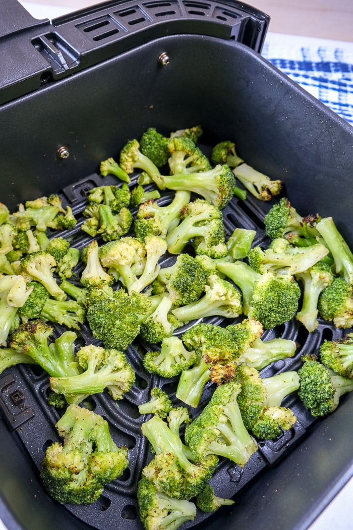 cooked broccoli in black air fryer tray