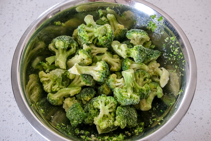 frozen broccoli in silver mixing bowl with oil and spices on top