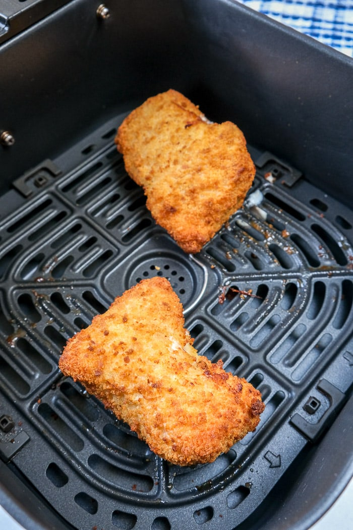 cooked breaded chicken cordon bleu in black air fryer tray