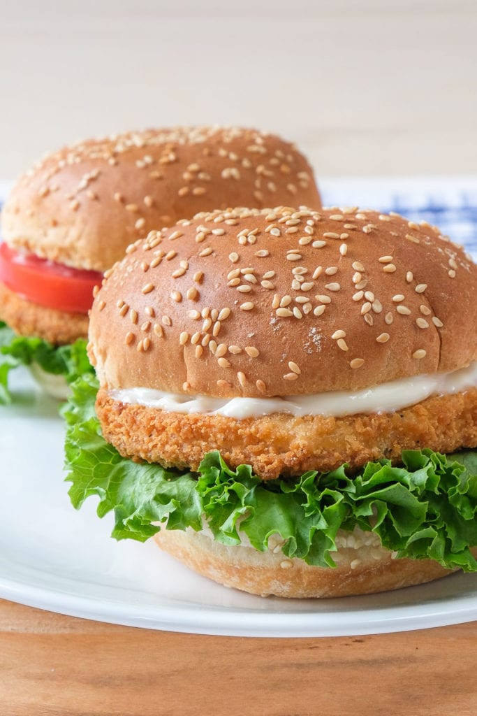 chicken patties in buns with lettuce on white plate