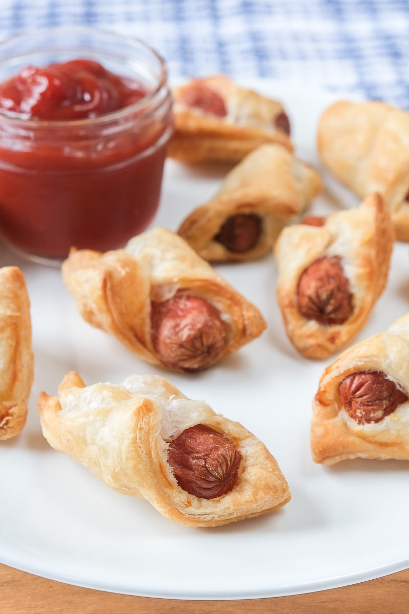 crispy pigs in a blanket on white plate with ketchup for dipping behind