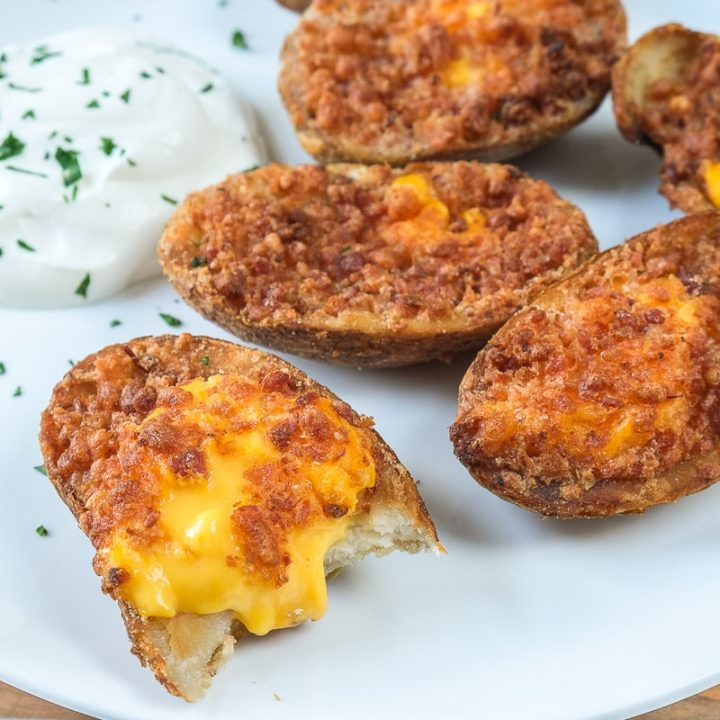 crispy potato skins on white plate with sour cream behind