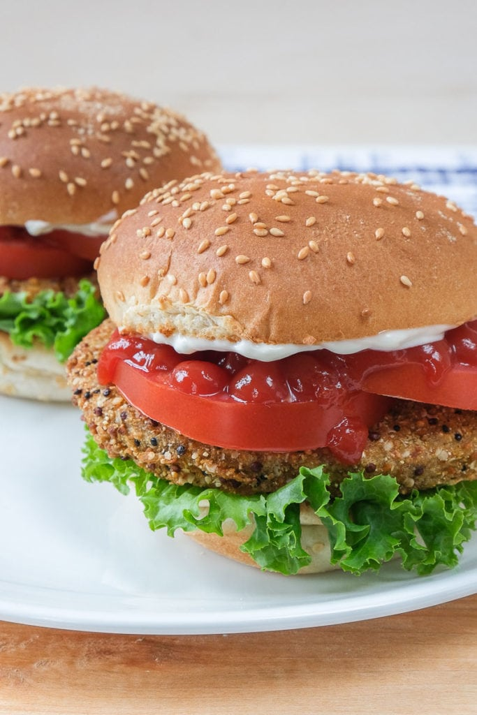 veggie burgers on buns with condiments on white plate