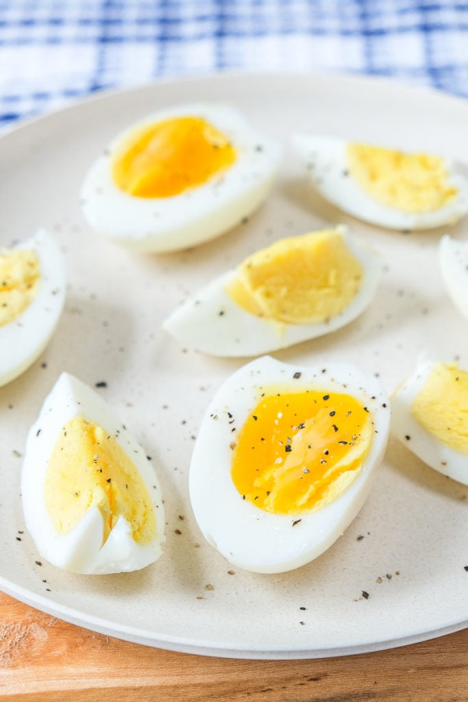 hard boiled eggs cut up on white plate with pepper