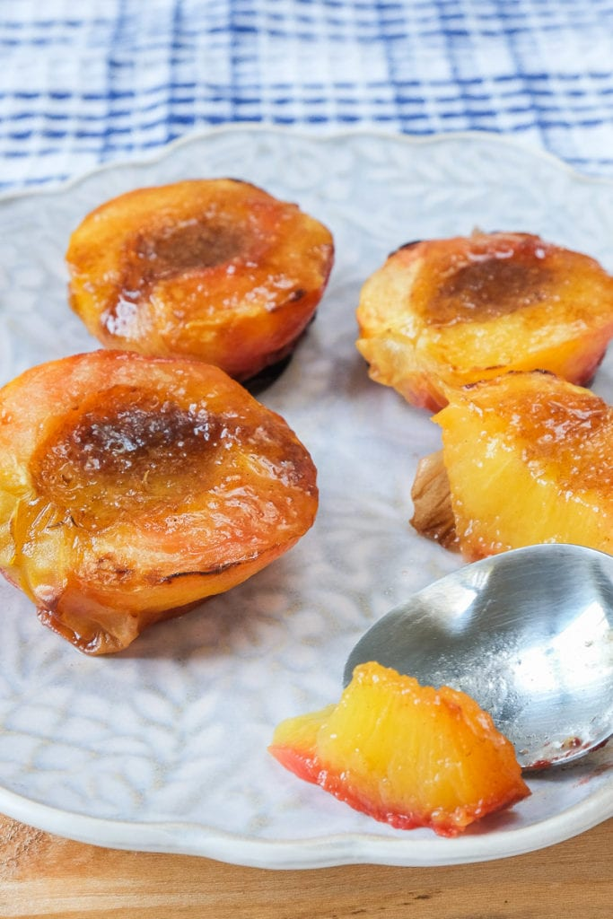 fried peaches on plate with silver spoon cutting into one