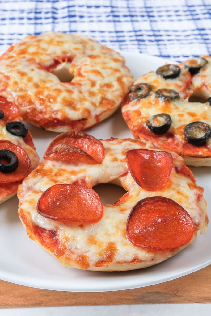 pizza bagels with cheese and pepperoni on white plate