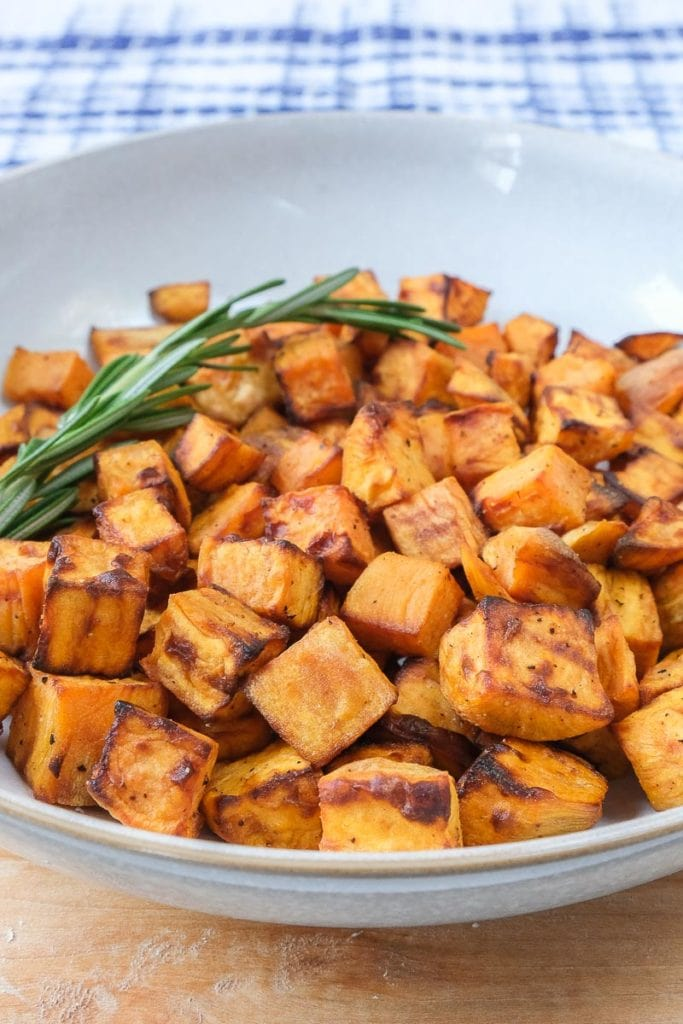 sweet potato cubes in bowl with rosemary behind