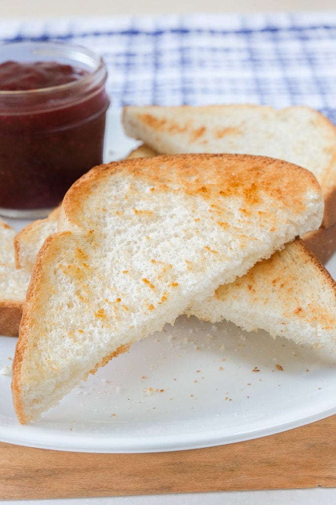 crispy toast pieces on white plate with jam behind