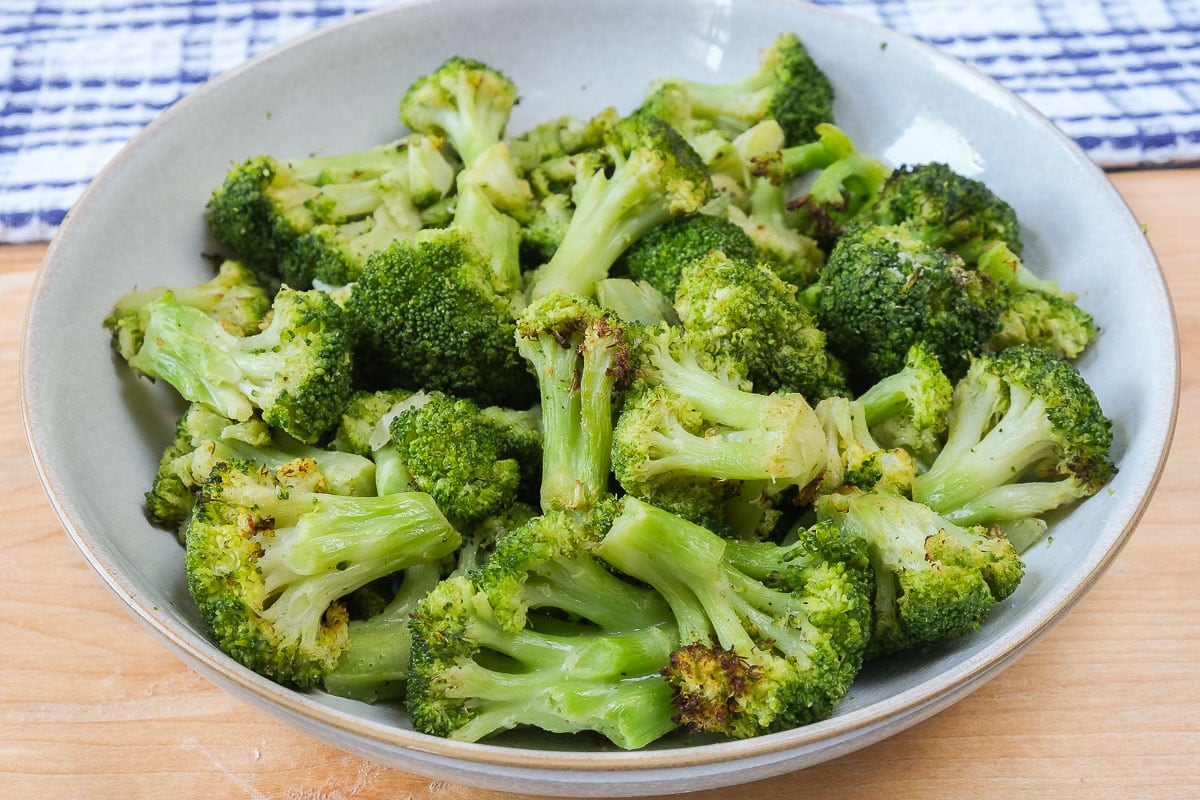bowl of green broccoli on wooden board