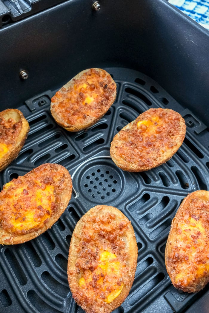 cooked cheesy potato skins in air fryer tray