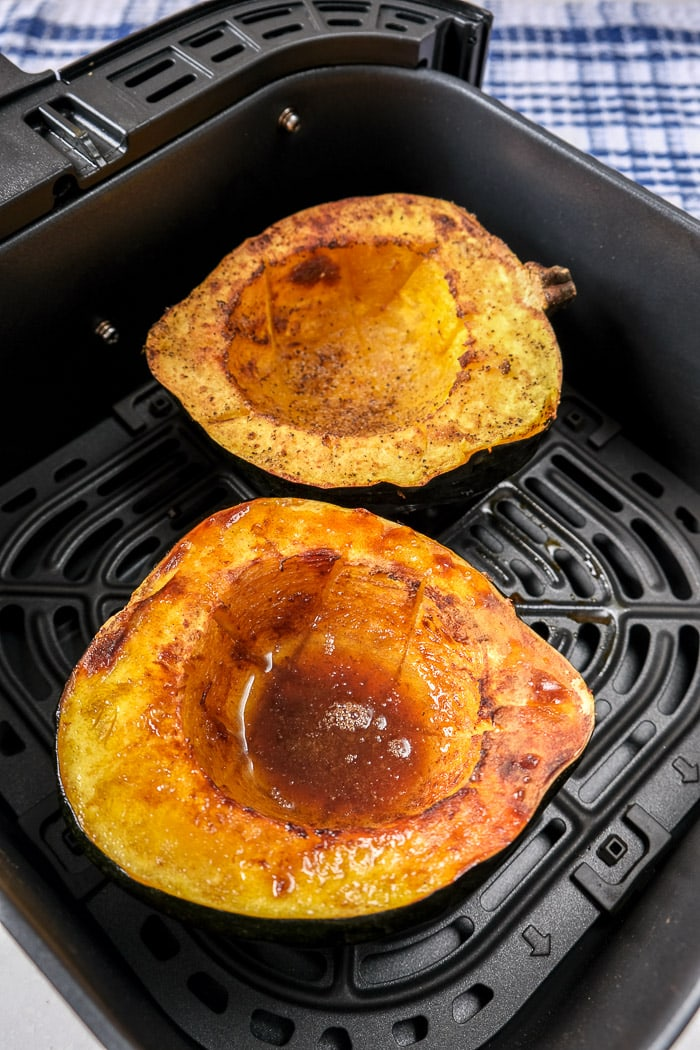 cooked halves of acorn squash in black air fryer basket on counter