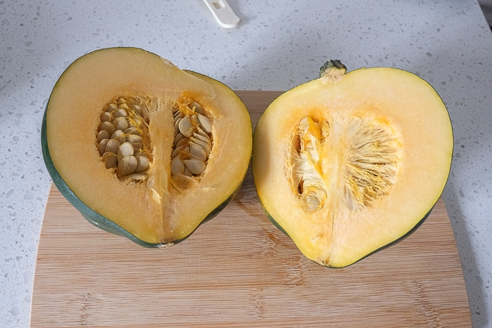 acorn squash cut in half on wooden cutting board on counter top