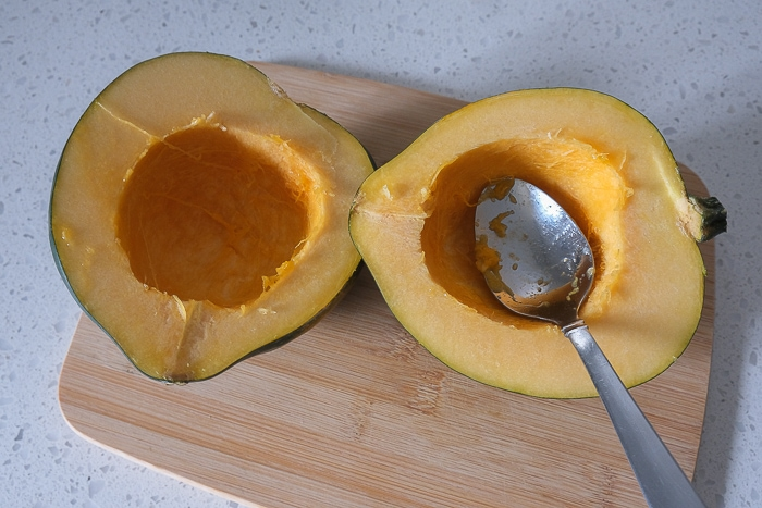 acorn squash cut in half with spoon in one on wooden board