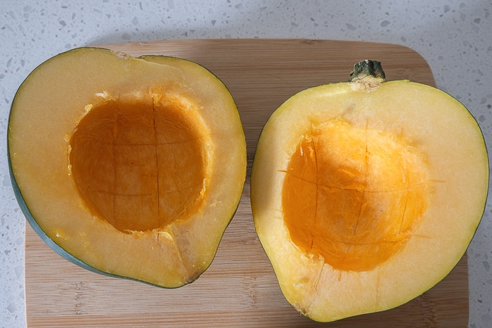 two halves of acorn squash with scoring inside on wooden cutting board