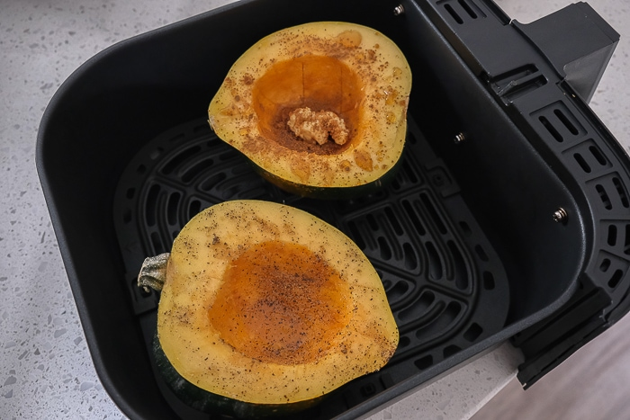 two halves of acorn squash in black air fryer tray on counter