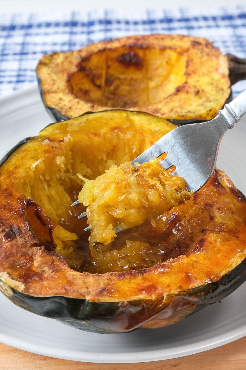 halves of cooked acorn squash on white plate with fork inside