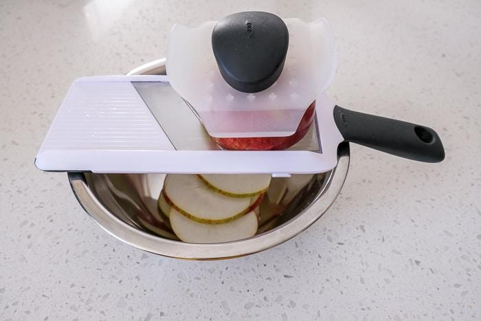mandolin slicer with apple on top of metallic bowl
