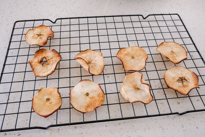 cooked apple chips resting on cooking tray on counter