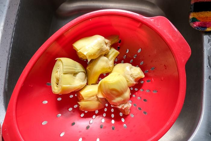 artichoke hearts in red strainer over metallic sink