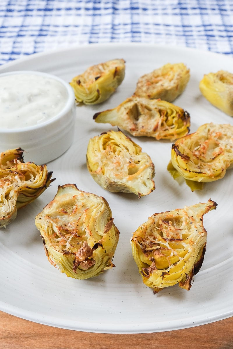 cooked artichoke hearts on white plate with dip beside