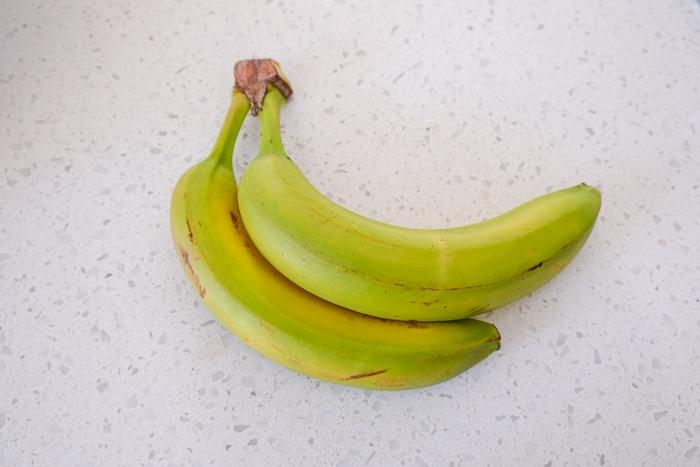 green bananas on white counter top