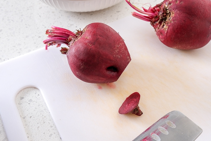 beets on white cutting board with ends cut off