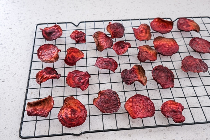 beet chips laying on cooling rack on white counter top