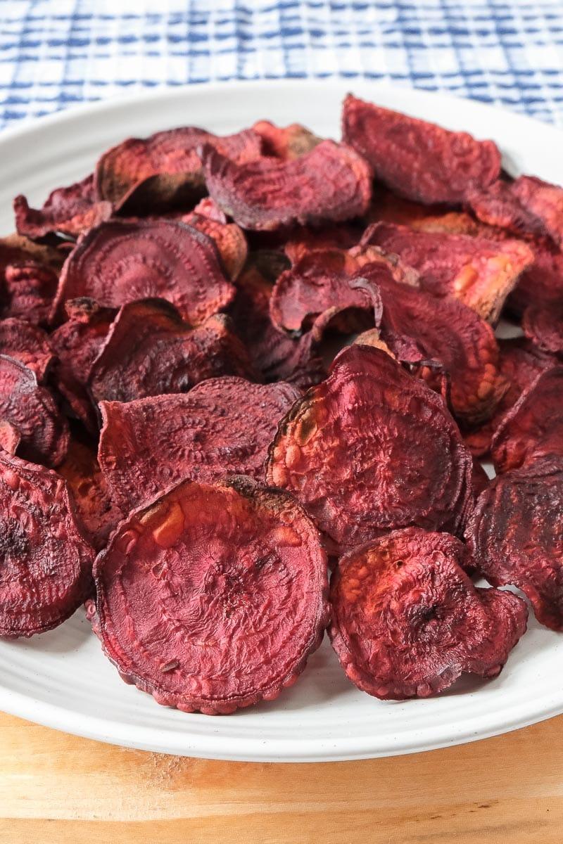 crispy beet chips on white plate on wooden board