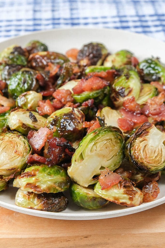 cooked brussels sprouts with bacon pieces on white plate on wooden board