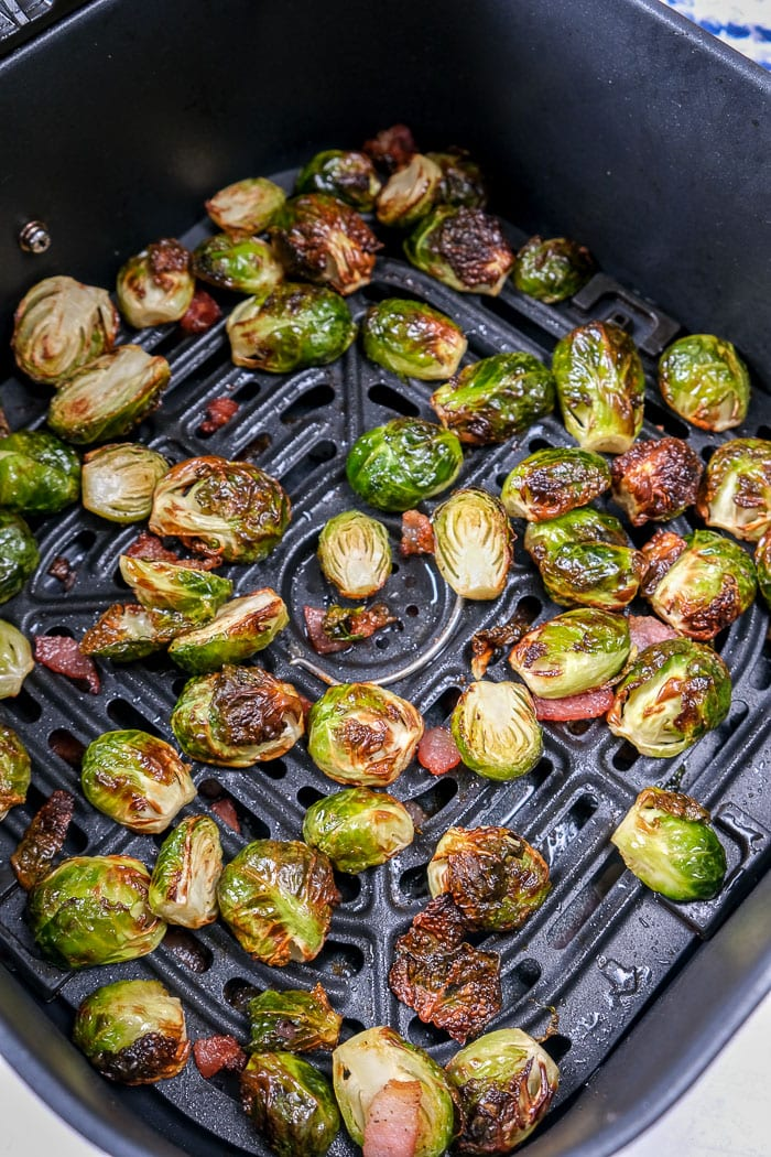 cooked brussels sprouts in black air fryer tray on counter