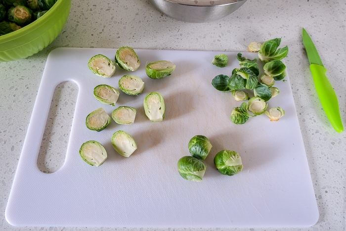 raw brussels sprouts on white cutting board with green knife beside