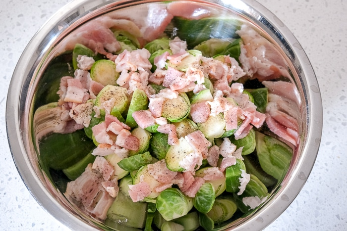 raw bacon added to silver bowl full of cut brussels sprouts on counter