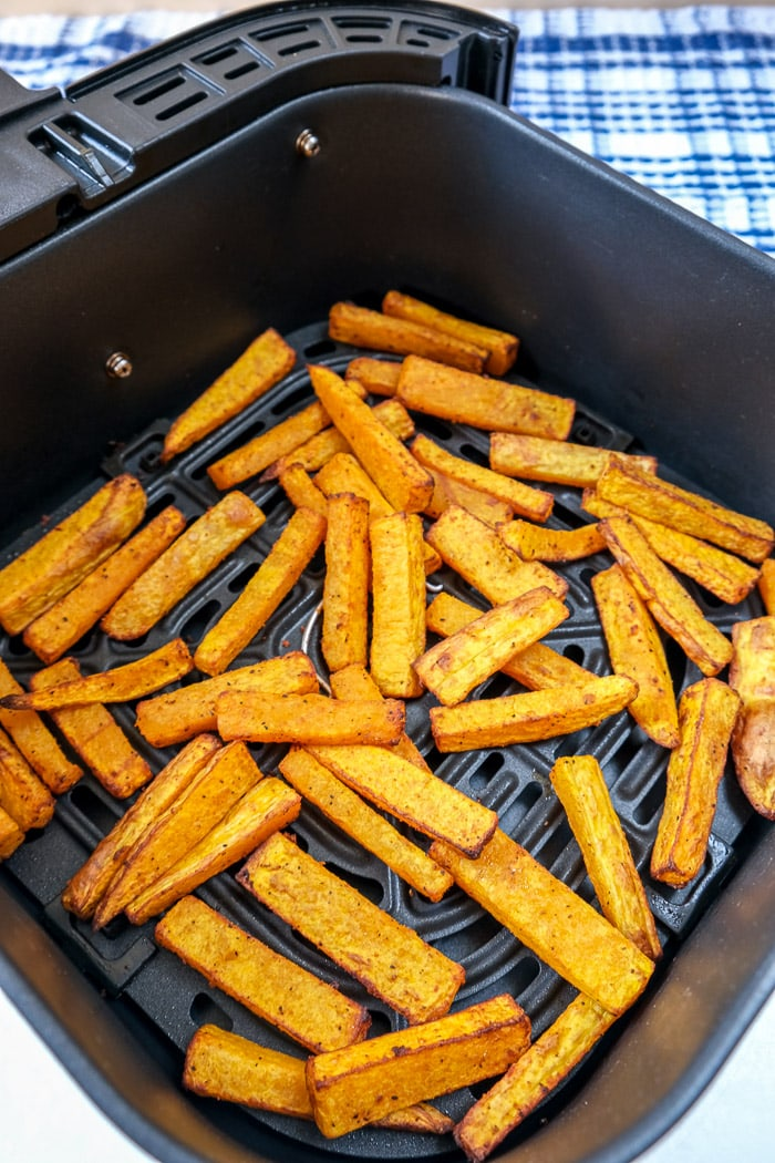 cooked butternut squash fries in black air fryer tray on white counter top