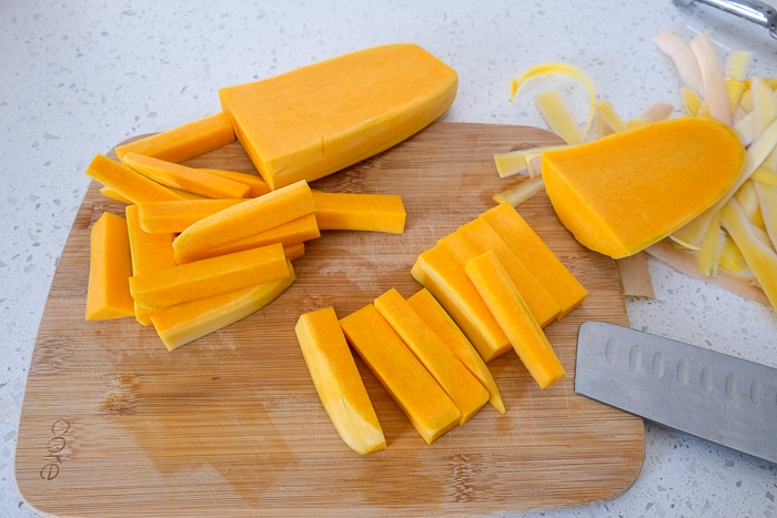 raw butternut squash fries on wooden cutting board on white counter