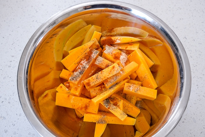 silver mixing bowl fill of raw butternut squash fries covered in spices