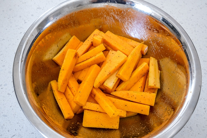 butternut squash fries in silver bowl coated in spices on white counter