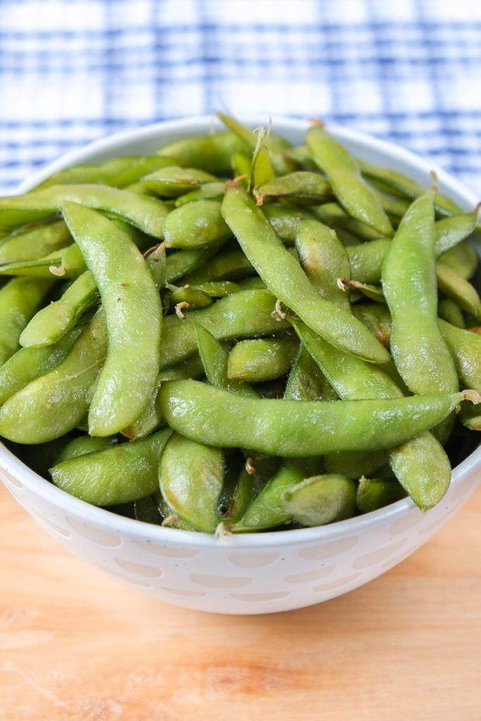 green edamame in bowl on wooden board with blue cloth behind