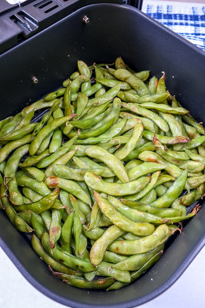 roasted edamame in black air fryer tray on counter top