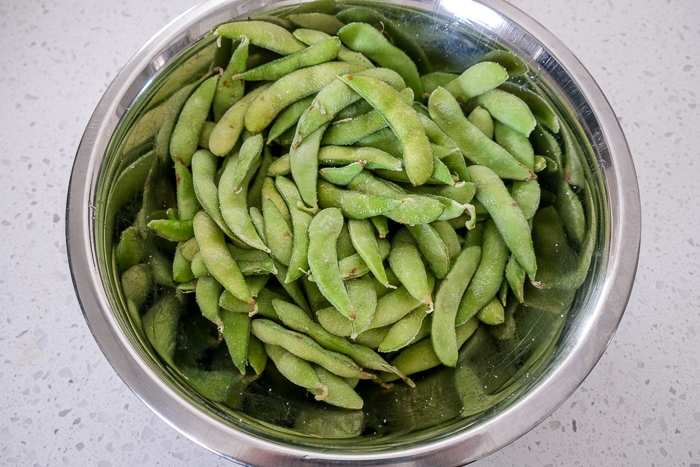 edamame in oil and salt in silver mixing bowl on counter