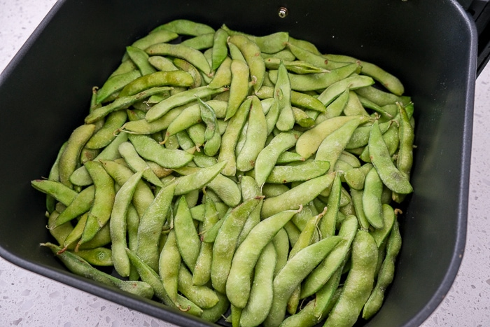 raw edamame with spices in black air fryer tray on counter