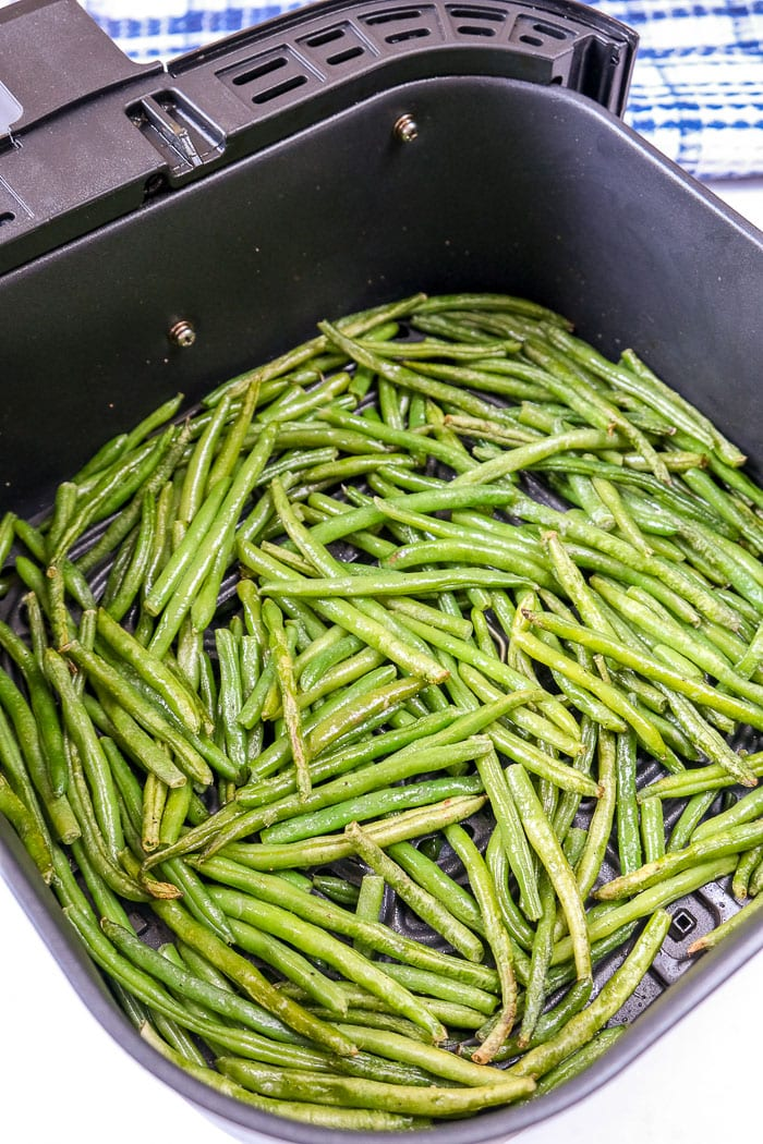 green beans cooked in black air fryer tray on counter top