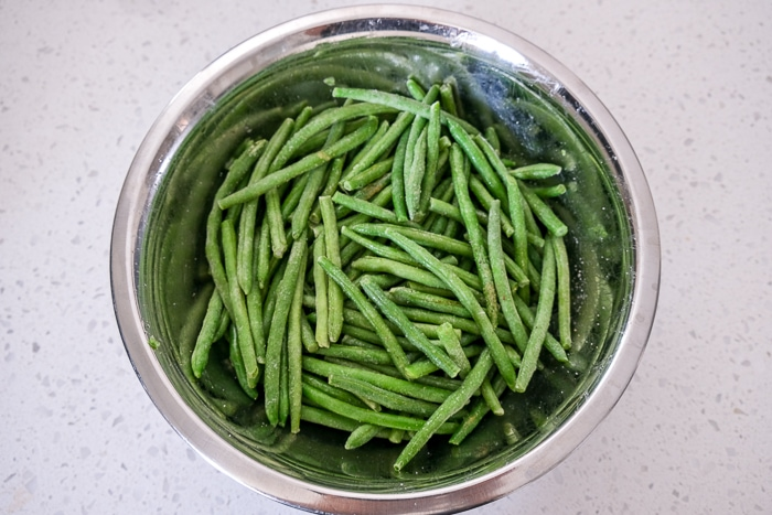 frozen green beans in silver bowl with oil and spices