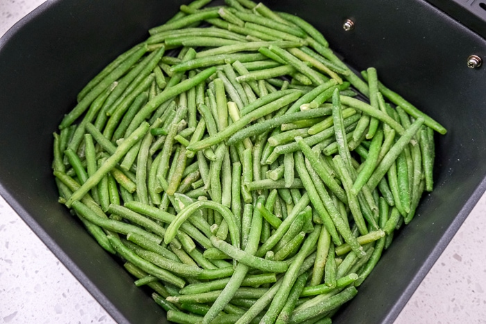green beans with spices in black air fryer tray