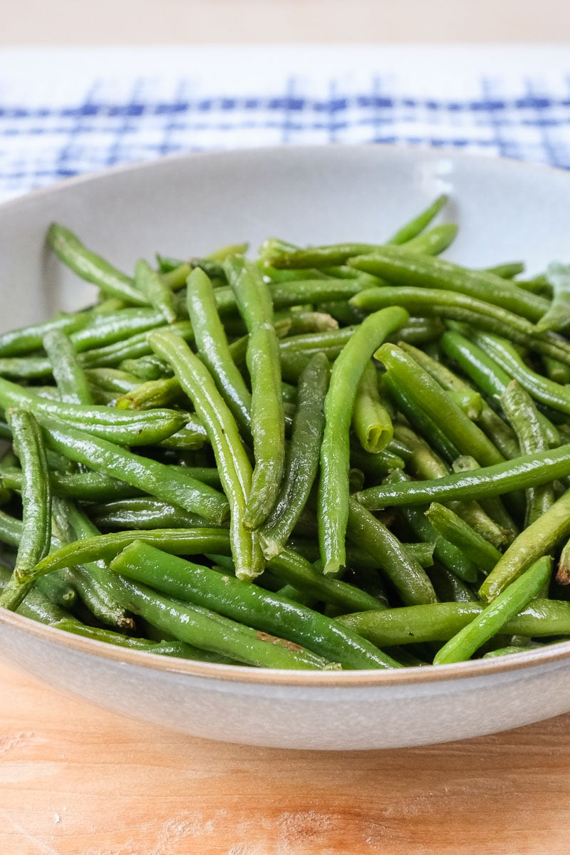 cooked green beans in bowl on wooden board