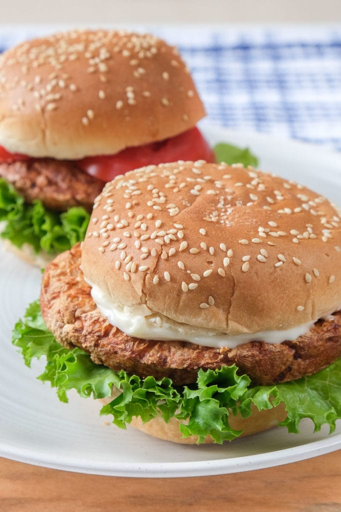 two turkey burgers on sesame buns on white plate on wooden board