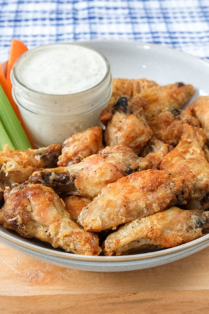parmesan chicken wings in bowl with dip and cut celery behind
