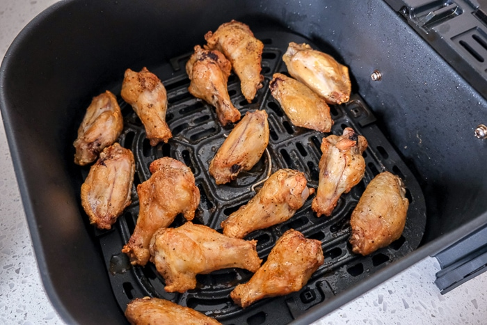 semi-cooked chicken wings in black air fryer tray on white counter